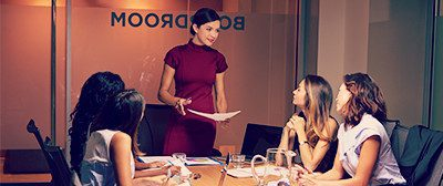 Five women sitting around a conference room table in a boardroom. One is standing and presenting